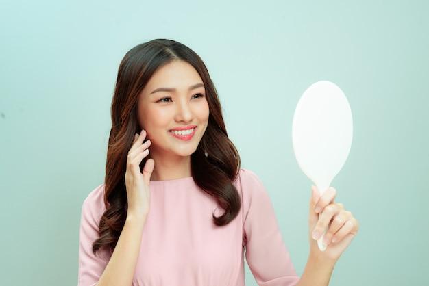 Femme prenant soin de sa belle peau et de son visage par miroir à la maison, beauté asiatique