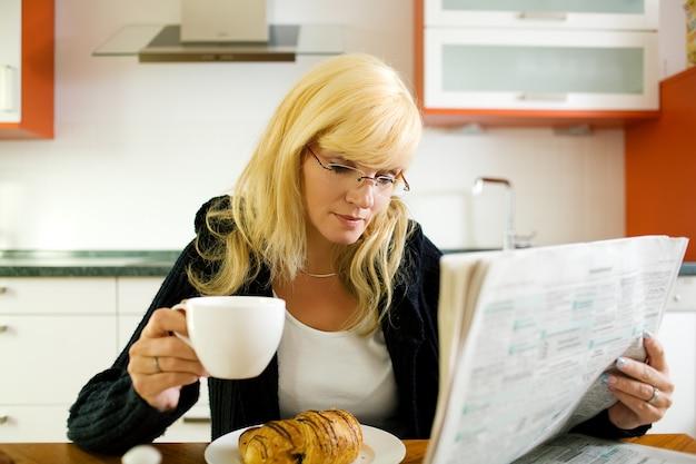 Femme prenant son petit déjeuner et lisant le journal