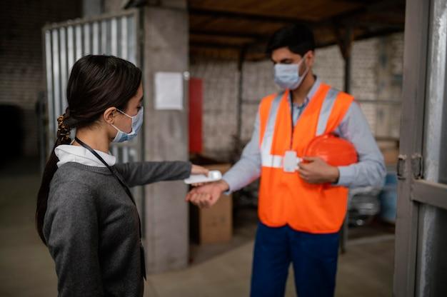 Femme prenant la température d'un collègue