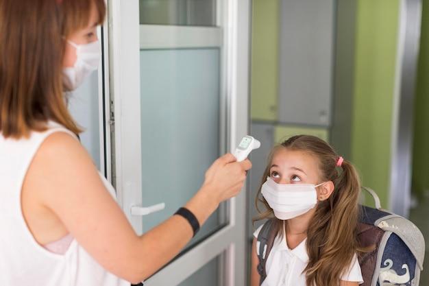 Femme prenant la température d'une petite fille