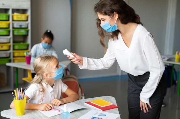 Femme prenant la température de son élève