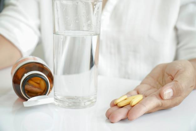 Femme prenant des vitamines, boit des suppléments.