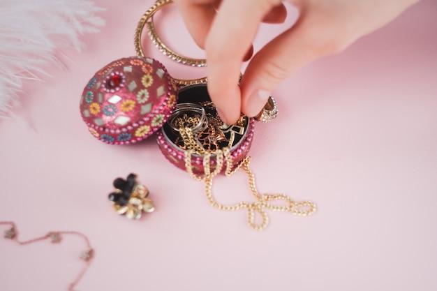 Femme prend des bijoux d'une petite boîte sur fond rose