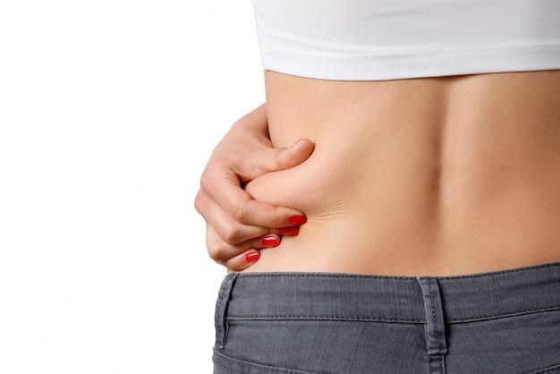 La femme prend de la graisse supplémentaire sur les côtés de son ventre avec sa main