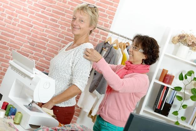 Femme prend des mesures sur le client avec un ruban à mesurer