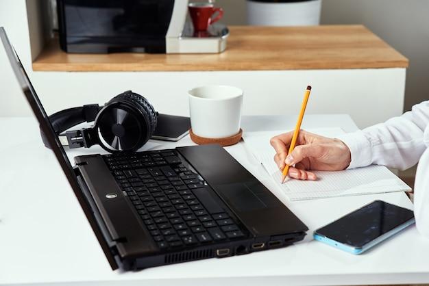 Femme prend des notes dans un cahier et utilise un ordinateur portable pour étudier