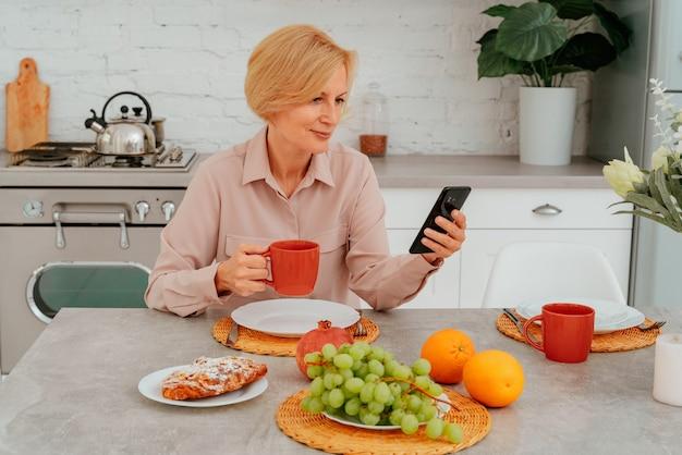 La femme prend le petit déjeuner à la maison avec le gâteau aux fruits et le café et lit des nouvelles du smartphone
