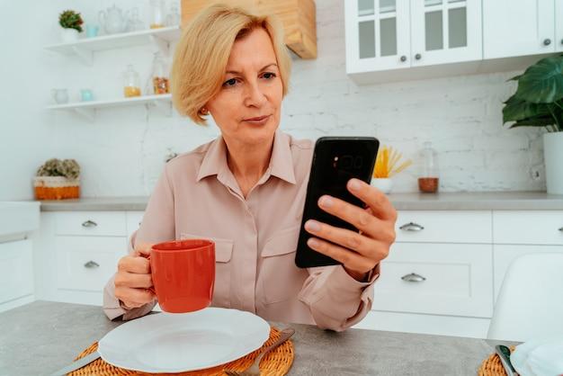 La femme prend le petit déjeuner à la maison et lit du smartphone