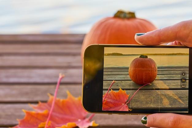 Une femme prend une photo de citrouille et de feuilles d'automne avec un lac en arrière-plan.