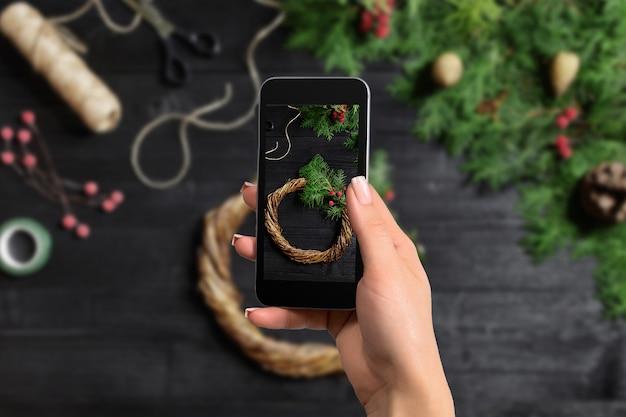 La femme prend la photo du décor de noël pour le réseau social