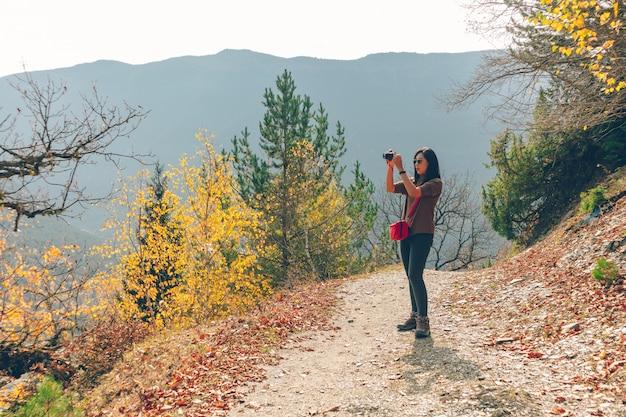 Une femme prend une photo de paysage naturel lors d'une randonnée sur la colline en automne.