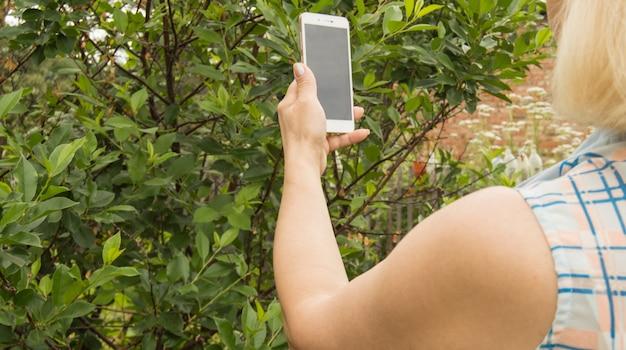 Une femme prend une photo avec un téléphone portable, prend des photos de plantes et d'arbres dans un jardin extérieur