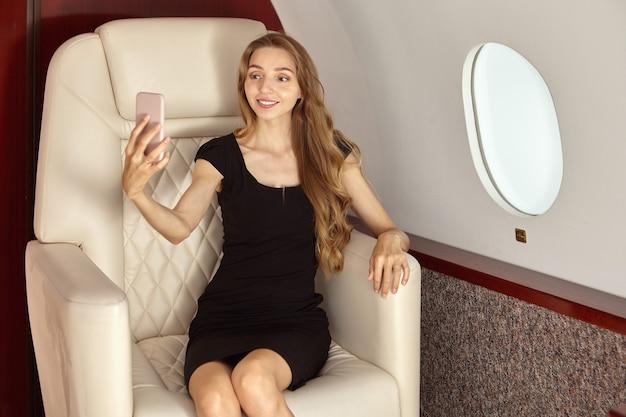 La femme prend des photos d'elle-même à l'intérieur de l'avion sur le siège passager près de la fenêtre.