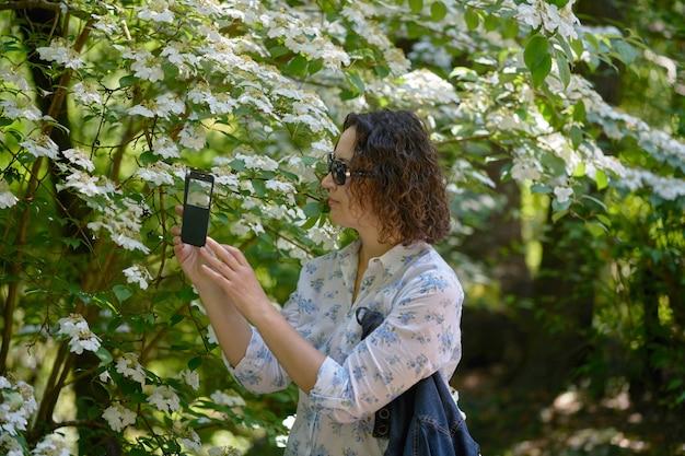 Une femme prend des photos de fleurs d'un viburnum.