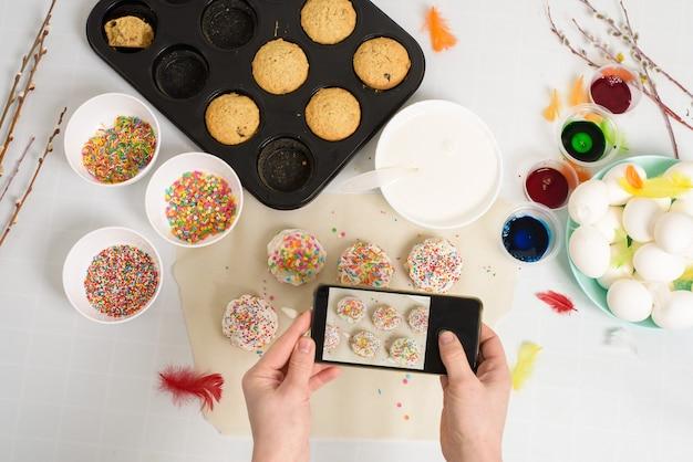 Femme prend des photos sur son téléphone de petits gâteaux cupcakes pour pâques avec glaçage blanc et bonbons sucrés, vue de dessus, branches de saule et oeufs à colorier