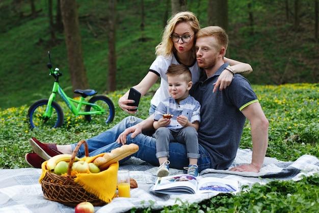 Femme prend un selfie avec ses parents et son fils assis sur un plaid dans le parc