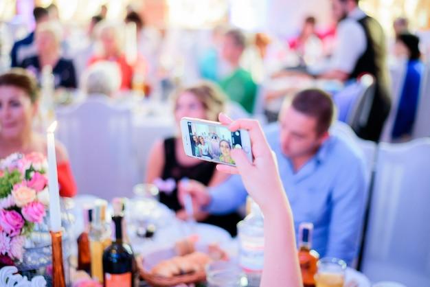 Femme prend selfie sur son iphone assis à la table du dîner