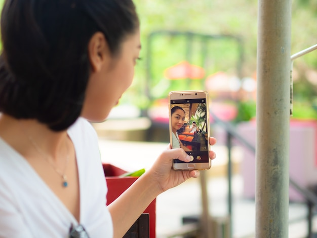 Femme prend selfie tendance avec son petit ami tenant la caméra.