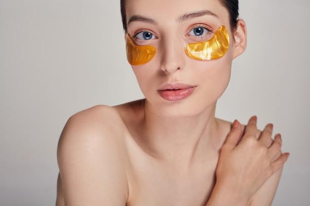 Une femme prend soin d'une peau délicate autour de ses yeux. procédures cosmétiques. soins de la peau du visage.