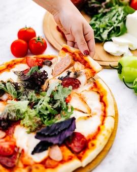 Femme prend une tranche de pizza mixte avec pepperoni, dinde à la saucisse et herbes