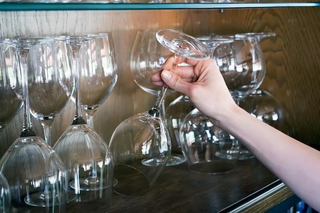 La femme prend un verre de l'étagère