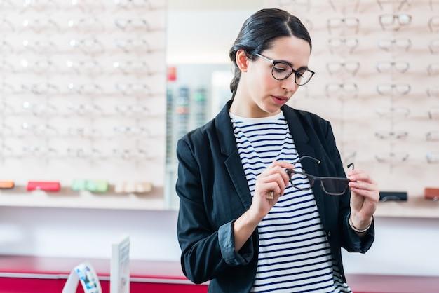 Femme, prendre, lunettes, hors plateau, dans, opticien, magasin