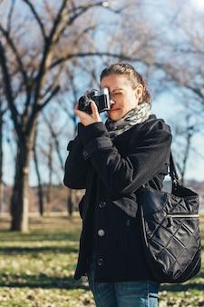 Femme, prendre photo, à, vieux, appareil-photo analogique