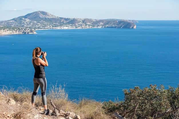 Femme à prendre des photos avec son appareil photo pour le paysage, dans la nature du peñon de ifach à calpe