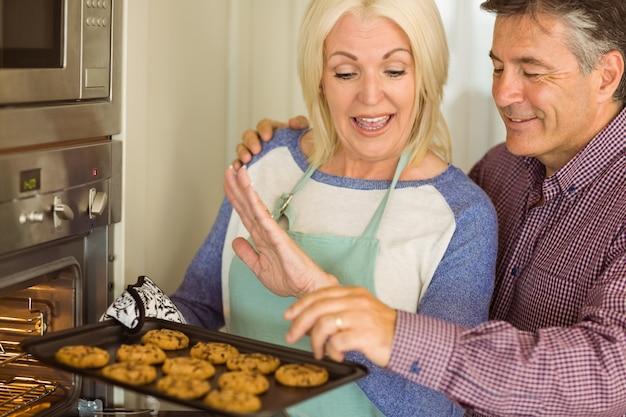 Femme, prendre, plateau, frais, cookies, sortir, four, mari