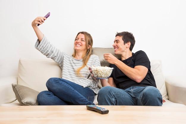 Femme, prendre, selfie, elle, à, petit ami, manger, pop-corn