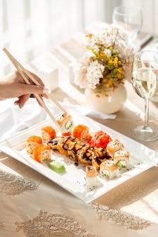 Femme, prendre, sushi, rouleaux, baguettes