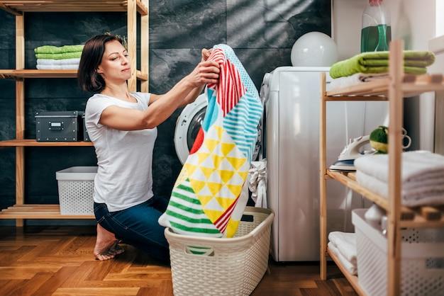 Femme, prendre, vêtements, machine à laver