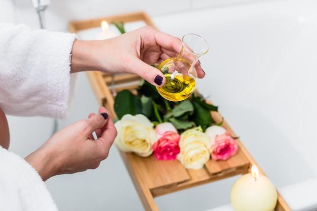 Femme préparant un bain de bien-être dans la baignoire.