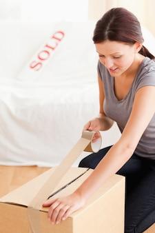 Femme préparant un carton pour le transport
