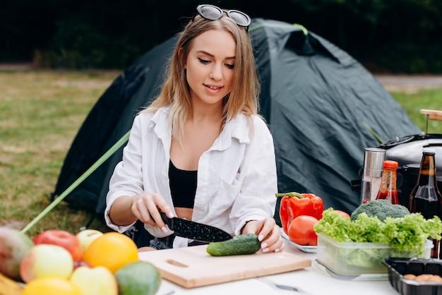 Femme préparant de la nourriture en plein air dans le camping