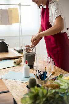 Femme préparant la pâte à papier dans un mélangeur