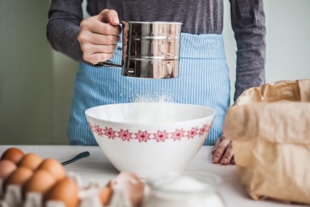 Femme préparant la pâte, tamisant la farine de blé dans un bol.focus sélectif