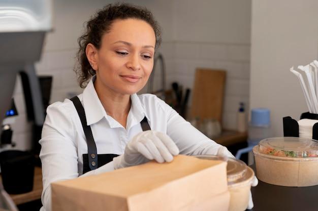 Femme préparant des plats à emporter à livrer
