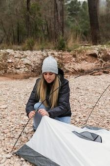 Femme préparant la tente pour le camping