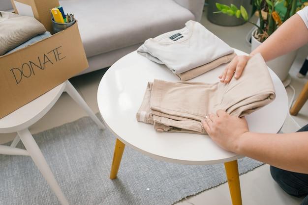 Femme préparant les vieux vêtements qu'elle veut donner pour la charité.