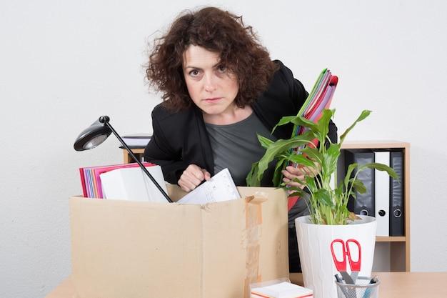 Femme prépare une boîte avec des fournitures de bureau