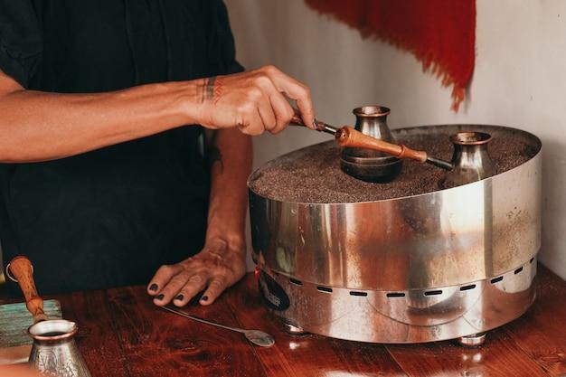 Une femme prépare un café sur le sable. gros plan de faire du café dans un turc. café d'ambiance traditionnel.