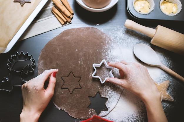Femme prépare les cookies dans le tableau noir du travail