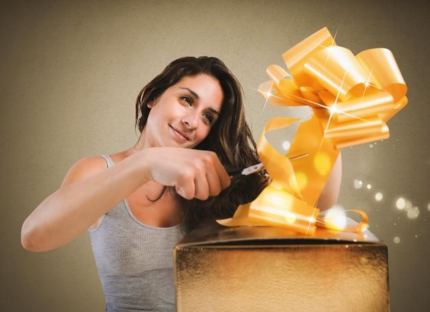 La femme prépare la décoration d'un paquet cadeau