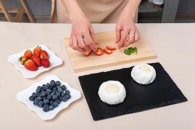 Femme prépare des gâteaux avec des fraises, des myrtilles et de la meringue. gâteau anna pavlova.