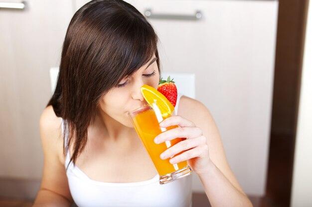 Femme prépare un jus de fruit avec un presse-agrumes