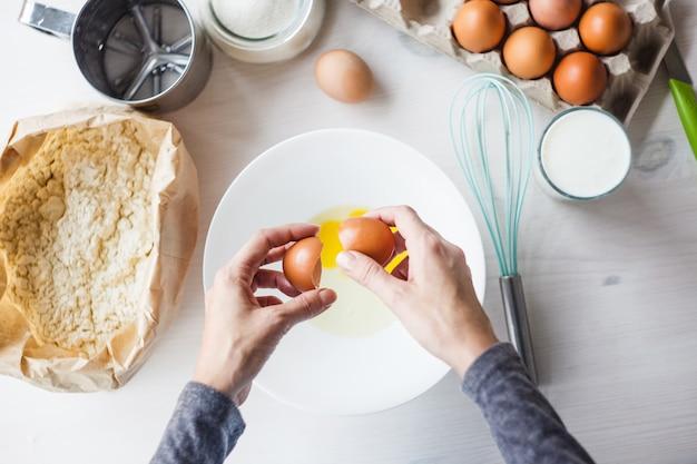 Une femme prépare la pâte pour la tarte, brise un œuf dans une tasse. ingrédients pour faire de la pâte.