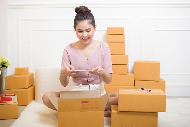 Une femme prépare des produits avec des boîtes en carton pour l'expédition.