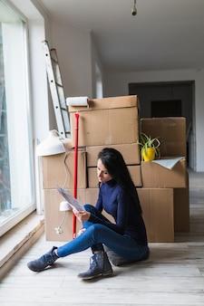 Femme près des boîtes et rouleau à peinture