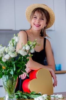 Femme près de bouquet de roses blanches dans un vase et une boîte cadeau